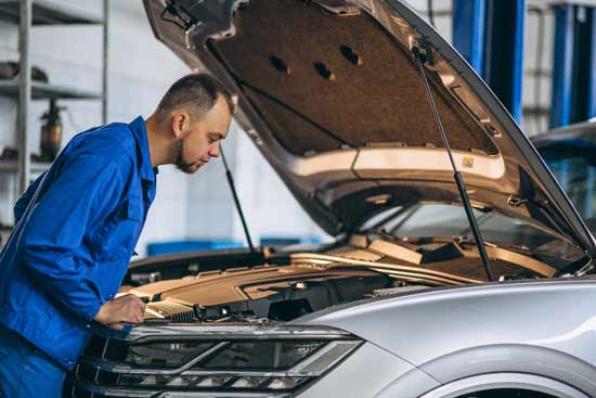 Un mecánico explora los elementos del coche eléctrico al pasar la ITV