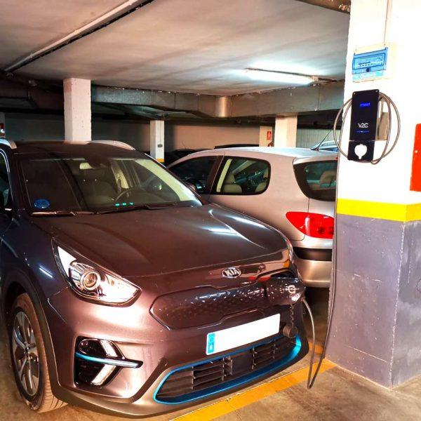 vehiculo electrico cargando en parking comunitario